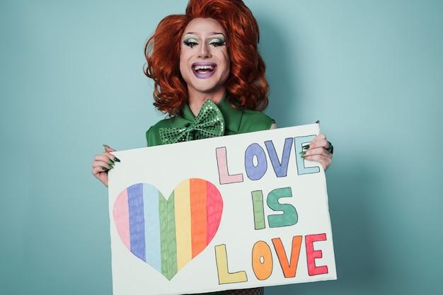 Szczęśliwa drag queen trzymająca baner dumy gejowskiej - lgbtq i koncepcja - skup się na twarzy