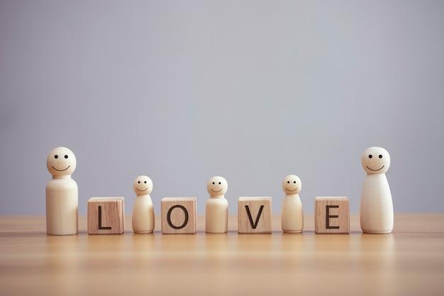 Szczęśliwa drewniana osoba z rodziny model buźkę ze słowem miłość na tle stołu z drewnianymi kostkami