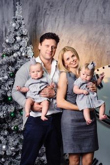 Szczęśliwa duża rodzina z bliźniakami w noworocznym wnętrzu domu na tle choinki.