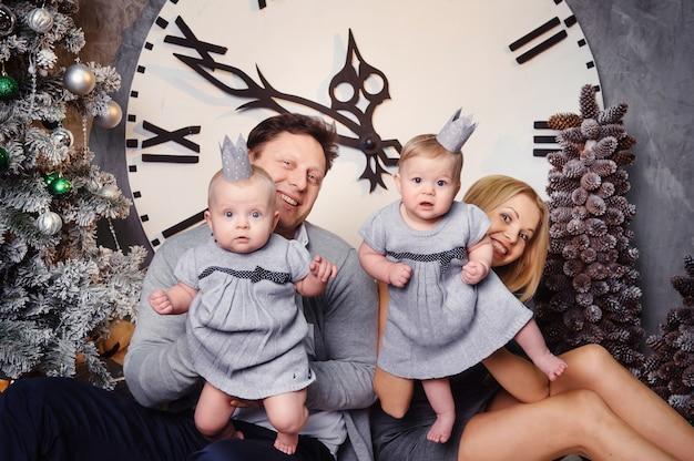 Szczęśliwa duża rodzina z bliźniakami w noworocznym wnętrzu domu na tle dużego zegara