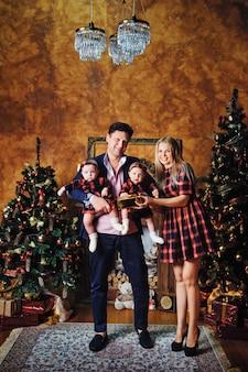 Szczęśliwa duża rodzina z dziećmi w noworocznym wnętrzu domu przy kominku przy choince