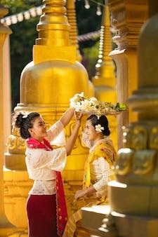 Szczęśliwa dwie kobiety w lokalnym stroju birmańskim pomagają przynosić kwiaty, aby zasłużyć w ważne dni pośród wielu złotych pagód.