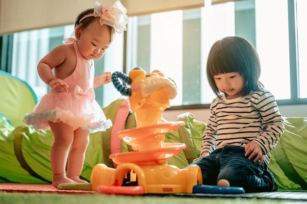 Szczęśliwa dwójka dzieci bawiła się razem bawiąc się zabawkamirodzina z dziećmi w domu miłość
