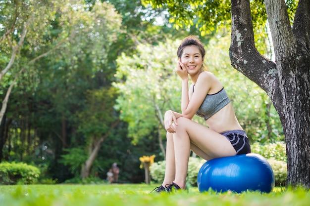 Szczęśliwa dysponowana młoda kobieta ćwiczy z sprawności fizycznej piłką w parku