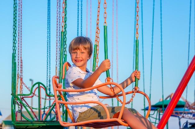 Szczęśliwa dziecko chłopiec ma zabawę w parku rozrywki. przejażdżka karuzelą łańcuchową.