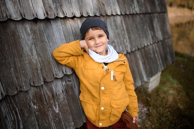Szczęśliwa dziecko chłopiec w ciepłej kurtce w jesieni. moda dziecięca, dzieciństwo, styl życia. wesołych świąt jesiennych.
