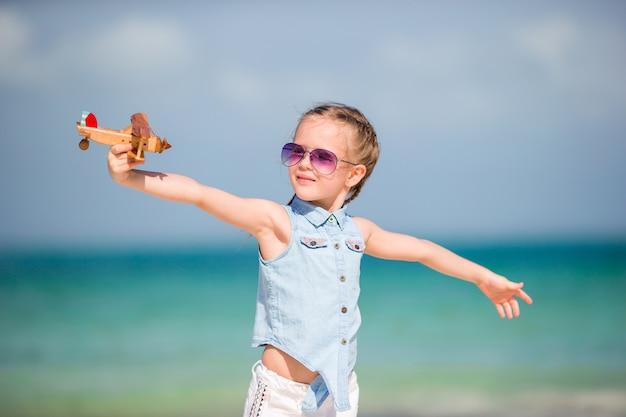 Szczęśliwa dziecko dziewczyna bawić się z zabawkarskim samolotem na plaży. dzieciak marzy o zostaniu pilotem