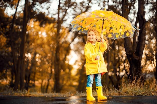 Szczęśliwa dziecko dziewczyna z parasolem i gumowymi butami jesień spacer