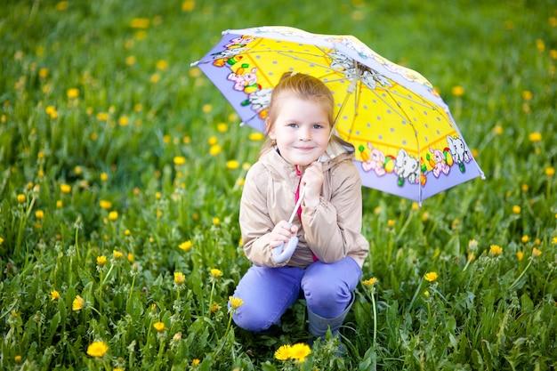 Szczęśliwa dziewczyna 5 lat pod żółtym parasolem chodzi po zielonej trawie po deszczu
