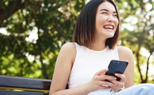 Szczęśliwa dziewczyna azjatyckich siedzi na ławce i przy użyciu telefonu komórkowego