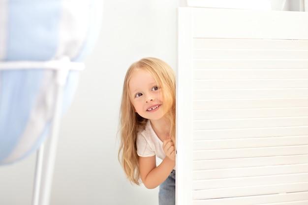 Szczęśliwa dziewczyna bawić się w chowanego w garderobie. aktywne dziecko szuka ukryć się za białymi drzwiami.