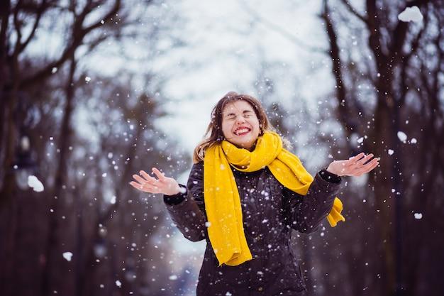 Szczęśliwa dziewczyna bawić się z śniegiem w parku