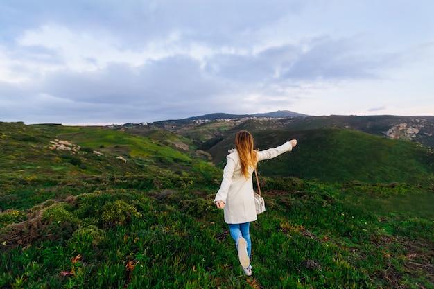Szczęśliwa dziewczyna biegnie na wzgórzach na wakacje