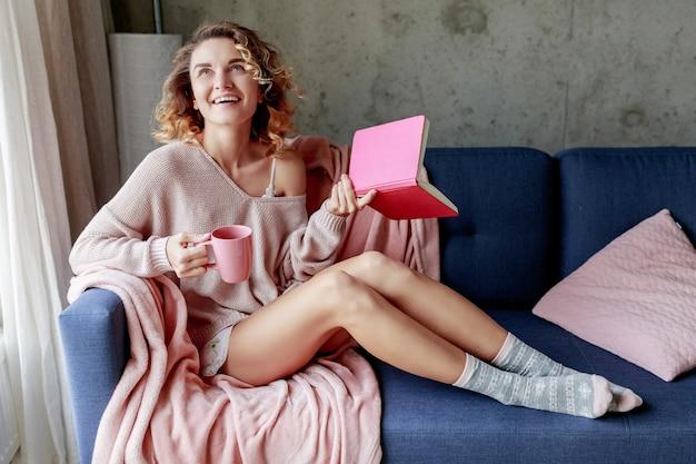 Szczęśliwa dziewczyna błogi, ciesząc się słoneczny poranek w domu, trzymając ulubioną książkę, pijąc kawę. ciepły, przytulny nastrój. różowe delikatne kolory.