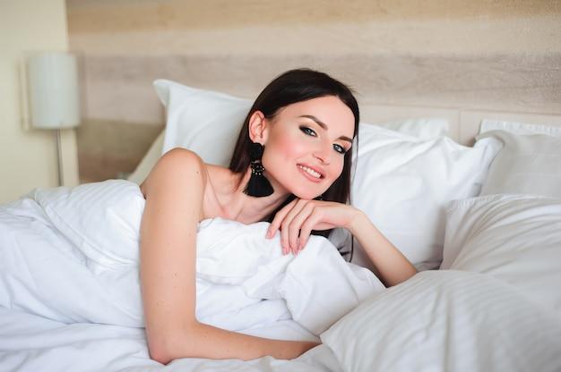 Szczęśliwa dziewczyna budzi się up rozciąganie ramiona na łóżku w nocy.