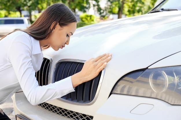 Szczęśliwa dziewczyna całuje jej samochód