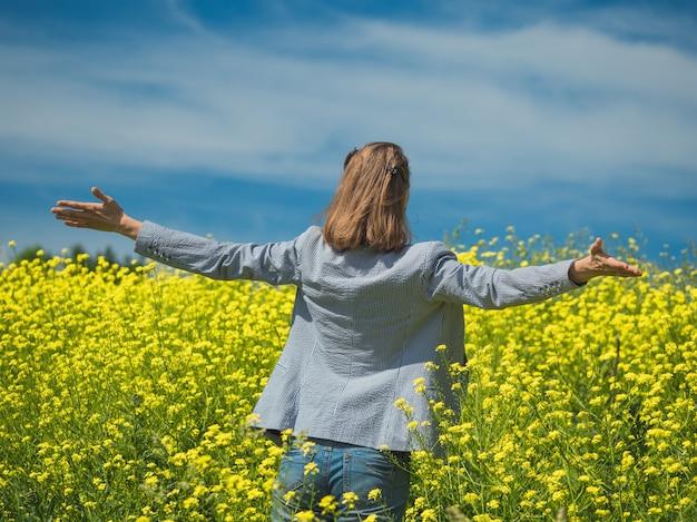 Szczęśliwa dziewczyna cieszy się piękno słoneczny letni dzień w polu żółci kwiaty
