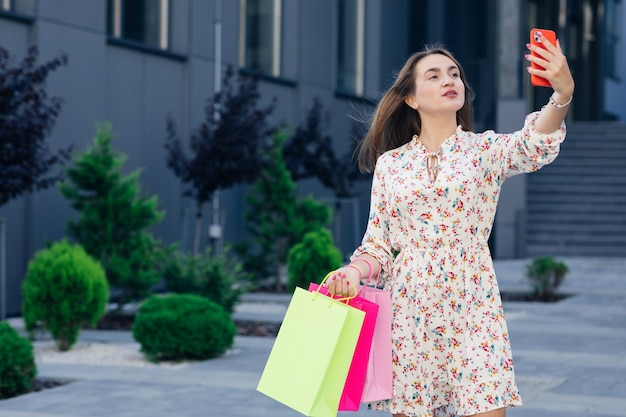 Szczęśliwa dziewczyna co selfie z mobilnego smartfona na świeżym powietrzu. influencerka społeczna bawiąca się na zakupach. koncepcja młodych ludzi i technologii nowej generacji stylu życia.