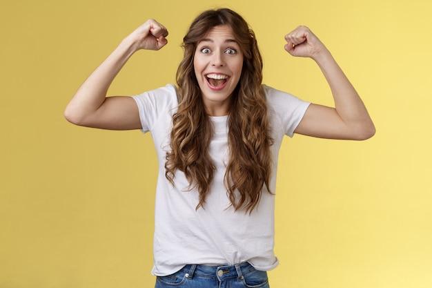 Szczęśliwa dziewczyna czuje się jak zwycięzca. triumfujący podekscytowany wesoła młoda kobieta podniósł ręce pięścią podniósł uroczysty uśmiech szeroko zachwycony krzycząc wspierający korzeń ulubionej drużyny osiągnąć sukces.