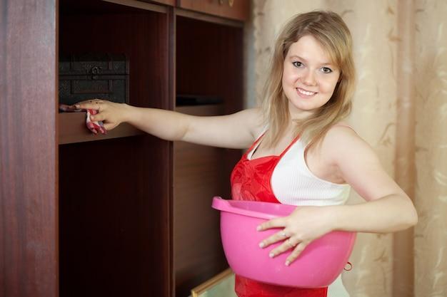 Szczęśliwa dziewczyna czyści meble