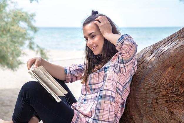 Szczęśliwa dziewczyna czyta książkę na drzewie, na plaży. osoba oderwana od wszystkiego. pojęcie relaksu i wyciszenia.