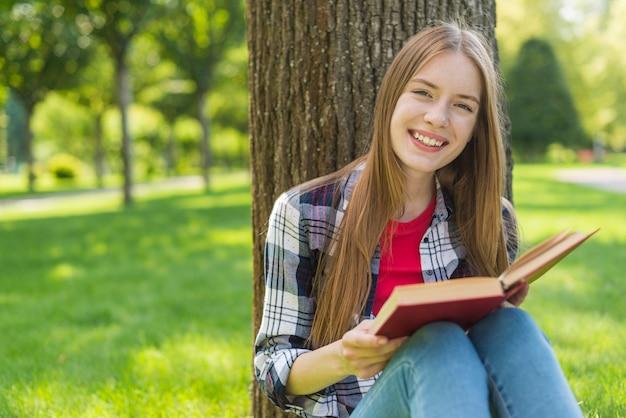 Szczęśliwa dziewczyna czyta książkę podczas gdy siedzący na trawie