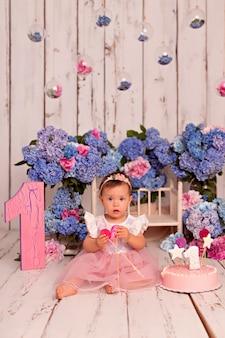 Szczęśliwa dziewczyna dziecko w sukience jedzenie tort urodzinowy