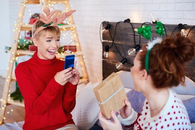 Szczęśliwa dziewczyna fotografuje domowe prezenty świąteczne