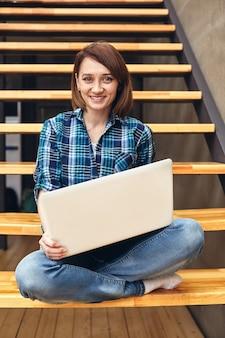 Szczęśliwa dziewczyna freelancer pracuje na laptopie w domu leśniczego