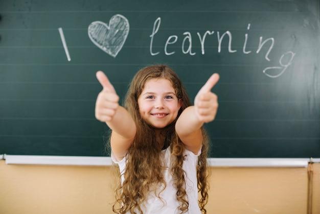 Szczęśliwa dziewczyna gestykuluje w klasie