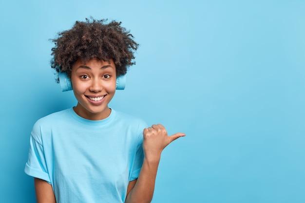 Szczęśliwa dziewczyna hipster z kręconymi włosami nosi słuchawki, słucha ścieżki dźwiękowej, ma wesołe punkty wyrazu, kciuk na bok pokazuje miejsce na kopię na treści reklamowe na białym tle nad niebieską ścianą. spójrz na to