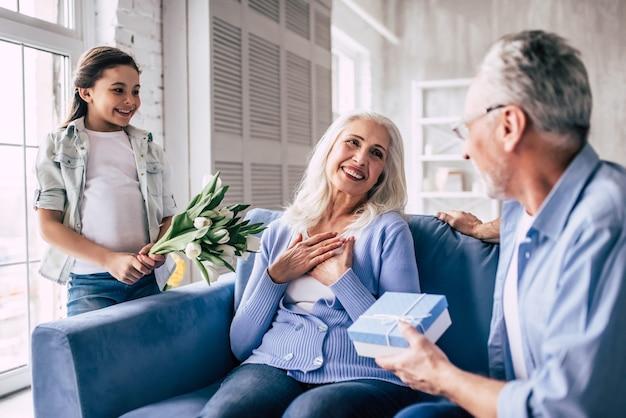 Szczęśliwa dziewczyna i dziadek dający kwiaty i prezent dla babci