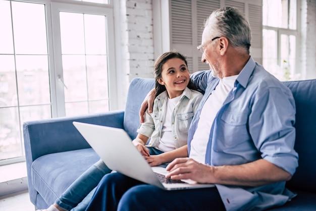 Szczęśliwa dziewczyna i dziadek korzystający z laptopa na kanapie