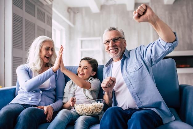 Szczęśliwa dziewczyna i dziadkowie oglądają telewizję i gestykulują