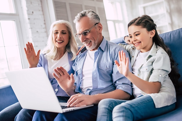 Szczęśliwa dziewczyna i dziadkowie siedzą z laptopem i gestykulują