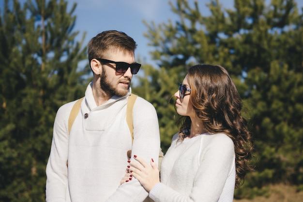 Szczęśliwa dziewczyna i facet z turystycznym plecakiem i gitarą, spacery w przyrodzie, koncepcja historii miłosnej podróży, selektywne focus