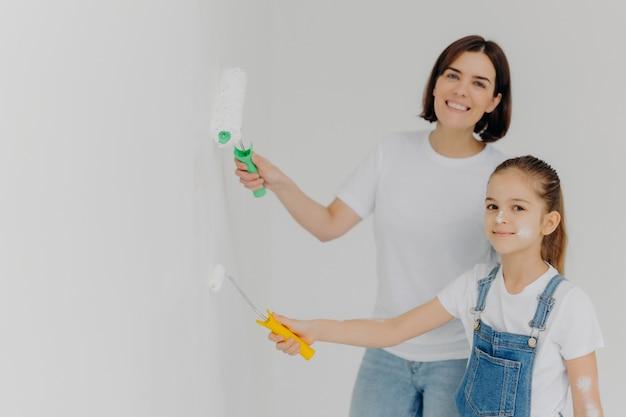 Szczęśliwa dziewczyna i jej matka malują ściany w białym kolorze za pomocą wałków malarskich