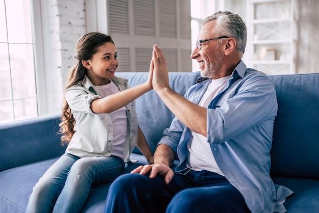 Szczęśliwa dziewczyna i pozdrowienie dziadka na kanapie
