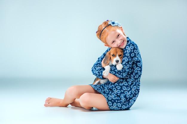 Szczęśliwa dziewczyna i szczeniak rasy beagle na szarej ścianie