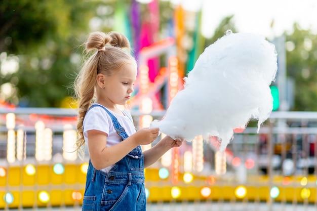 Szczęśliwa dziewczyna jedzenie waty cukrowej w parku rozrywki w lecie