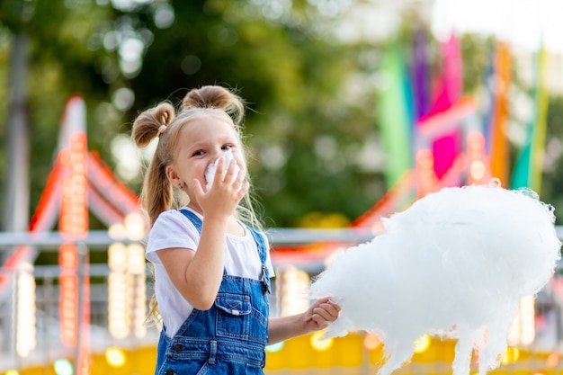 Szczęśliwa dziewczyna jedzenie waty cukrowej w parku rozrywki