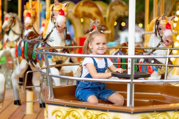 Szczęśliwa dziewczyna jedzie na karuzeli w parku rozrywki