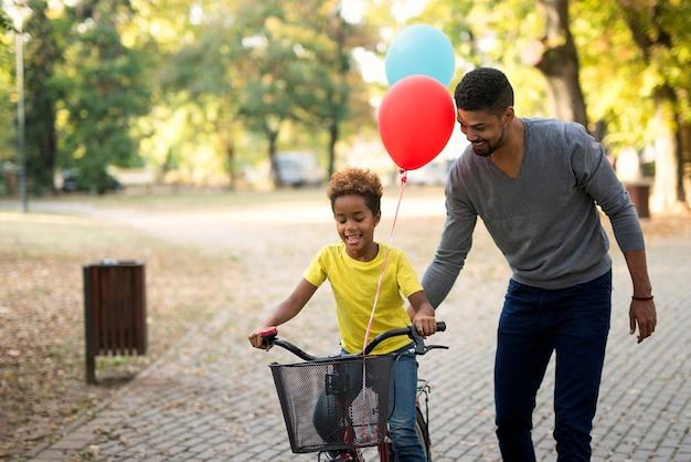 Szczęśliwa dziewczyna jedzie na rowerze, podczas gdy ojciec ją uczy