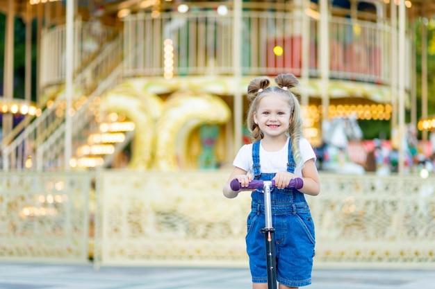 Szczęśliwa dziewczyna jedzie na skuterze w lecie w parku rozrywki