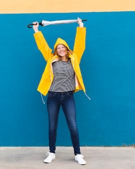 Szczęśliwa dziewczyna jest ubranym żółtego deszczowiec
