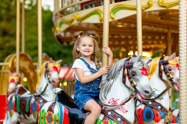 Szczęśliwa dziewczyna jeździ karuzelą na koniu w parku rozrywki