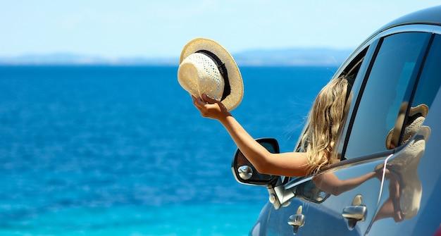 Szczęśliwa dziewczyna kierowcy z kapeluszem w samochodzie na morzu w lecie koncepcja wolności i szczęśliwej panoramy