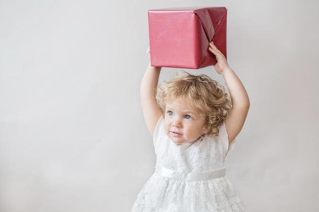 Szczęśliwa dziewczyna kręcone w białej sukni z prezentem na jasnoszarej ścianie