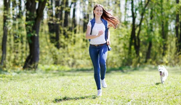 Szczęśliwa dziewczyna lekkoatletycznego bieganie z psem w parku