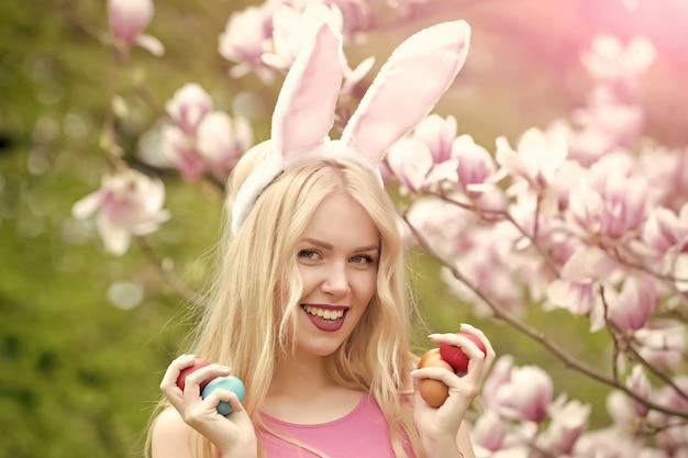 Szczęśliwa dziewczyna lub śliczna kobieta z pisankami, uszy królika na kwitnącej magnolii. wiosna. wielkanoc. święta, uroczystości.
